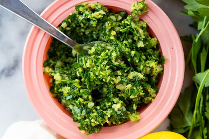 getting some Italian Gremolata from pink saucer plate using a spoon