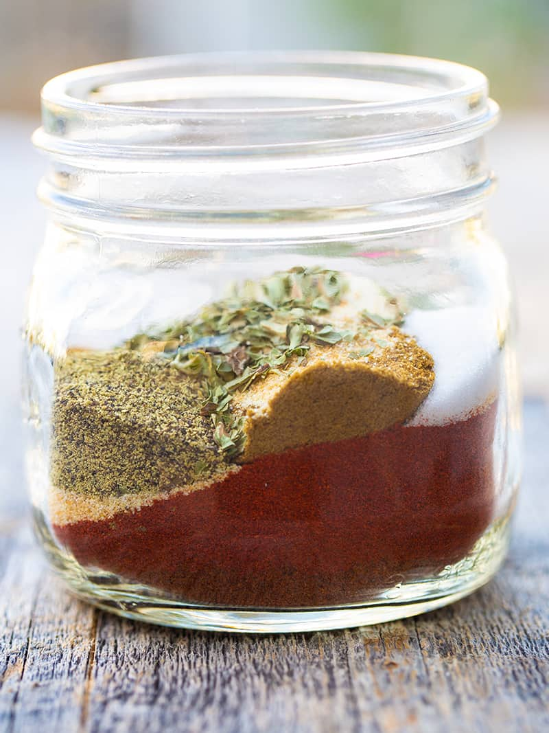 Taco Seasoning with chipotle powder, crushed red pepper flakes and cornstarch in a small clear glass container