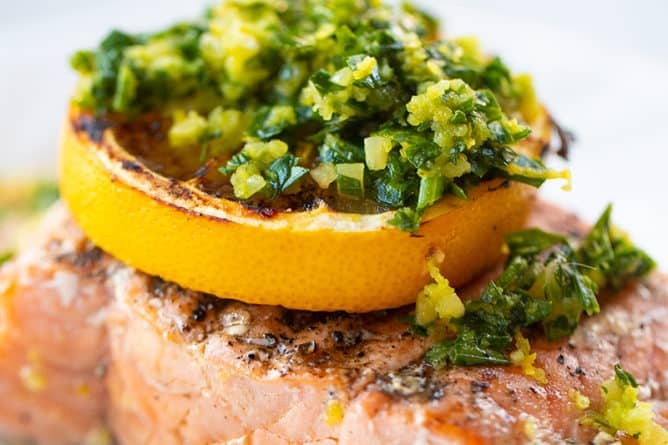 close up a piece of grilled salmon fillet with a slice of lemon and gremolata on top