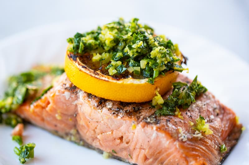a piece of grilled salmon fillet with a slice of lemon and gremolata on top