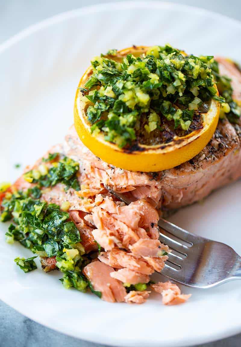 using a fork in flaking a slice of grilled salmon fillet with a slice of lemon and gremolata on top
