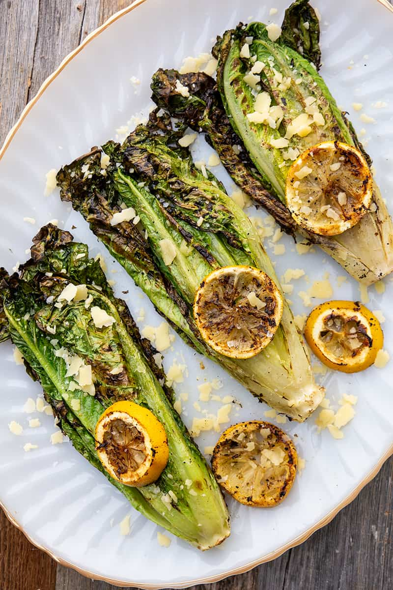 3 pieces of Parmesan Garlic Grilled Romaine in a white plate with some lemon slices on top and parmesan garlic toppings