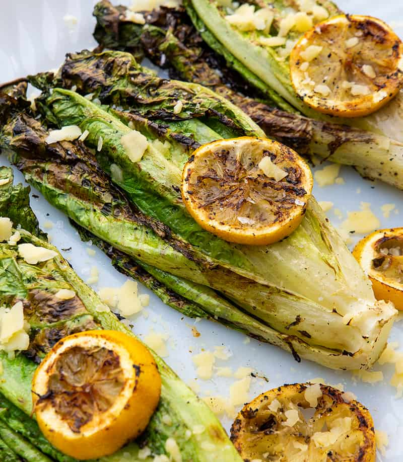 close up Parmesan Garlic Grilled Romaine with some lemon slices on top and parmesan garlic toppings