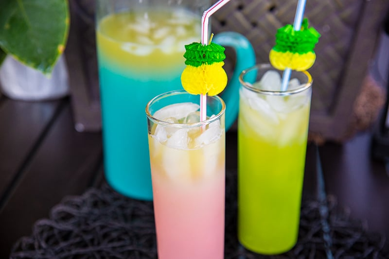 glasses of Pineapple Prosecco Party Punch with ice cubes, large pitcher with Pineapple Prosecco on the background