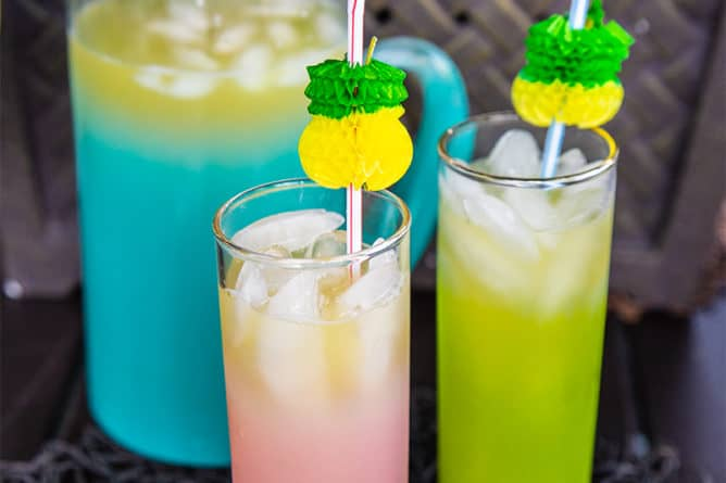 2 glasses and a large pitcher of Pineapple Prosecco Party Punch with ice cubes