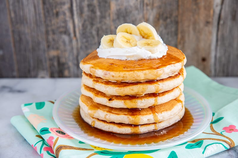 fluffy banana pancakes layer on a plate with maple syrup, whipped cream and sliced bananas on top
