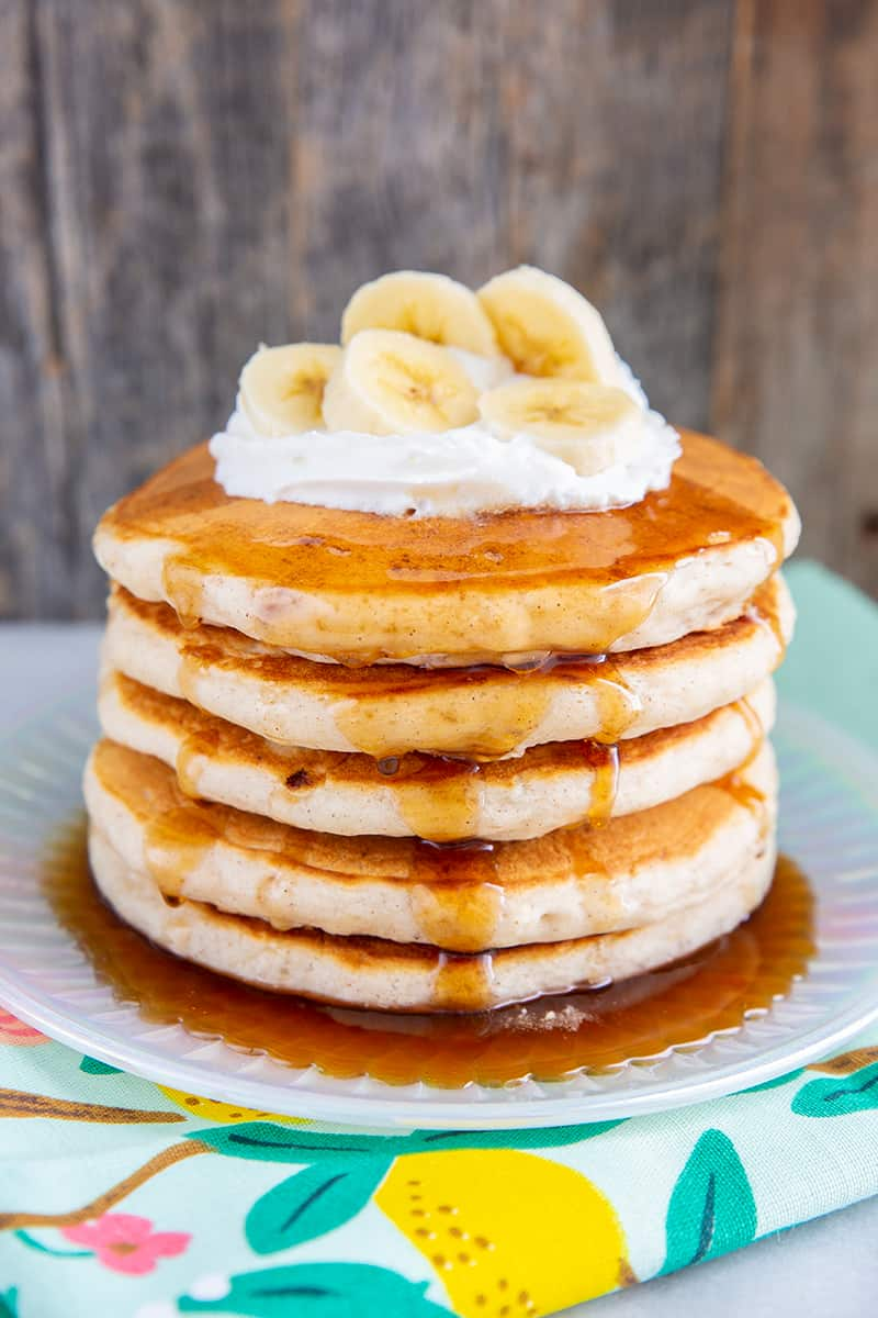 close up fluffy banana pancakes layer on a plate with maple syrup, whipped cream and sliced bananas on top