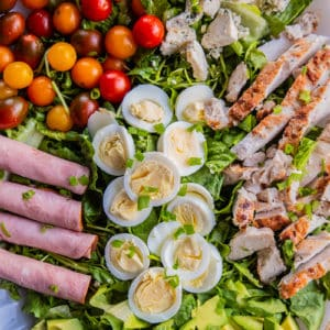 close up plate of Classic Cobb Salad - romaine lettuce, watercress, sliced hard boiled eggs, cherry tomatoes and all other ingredients