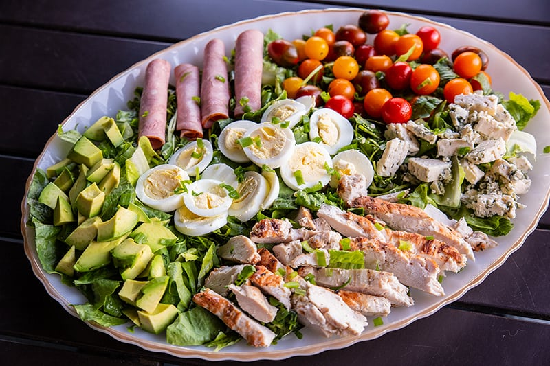 a plate of Classic Cobb Salad - romaine lettuce, watercress, sliced hard boiled eggs, cherry tomatoes and all other ingredients