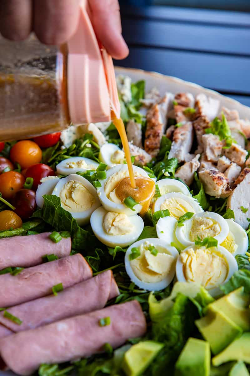 adding the salad dressing to a platter of Classic Cobb Salad