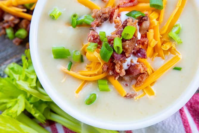 close up Super thick Cream of Celery Soup topped with shredded cheese, bacon bits and green onions in a white soup bowl. Raw celery stem and some toppings on its background