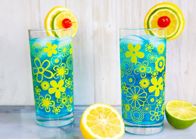 glasses filled with Electric Lemonade garnish with a slices of lemon and lime