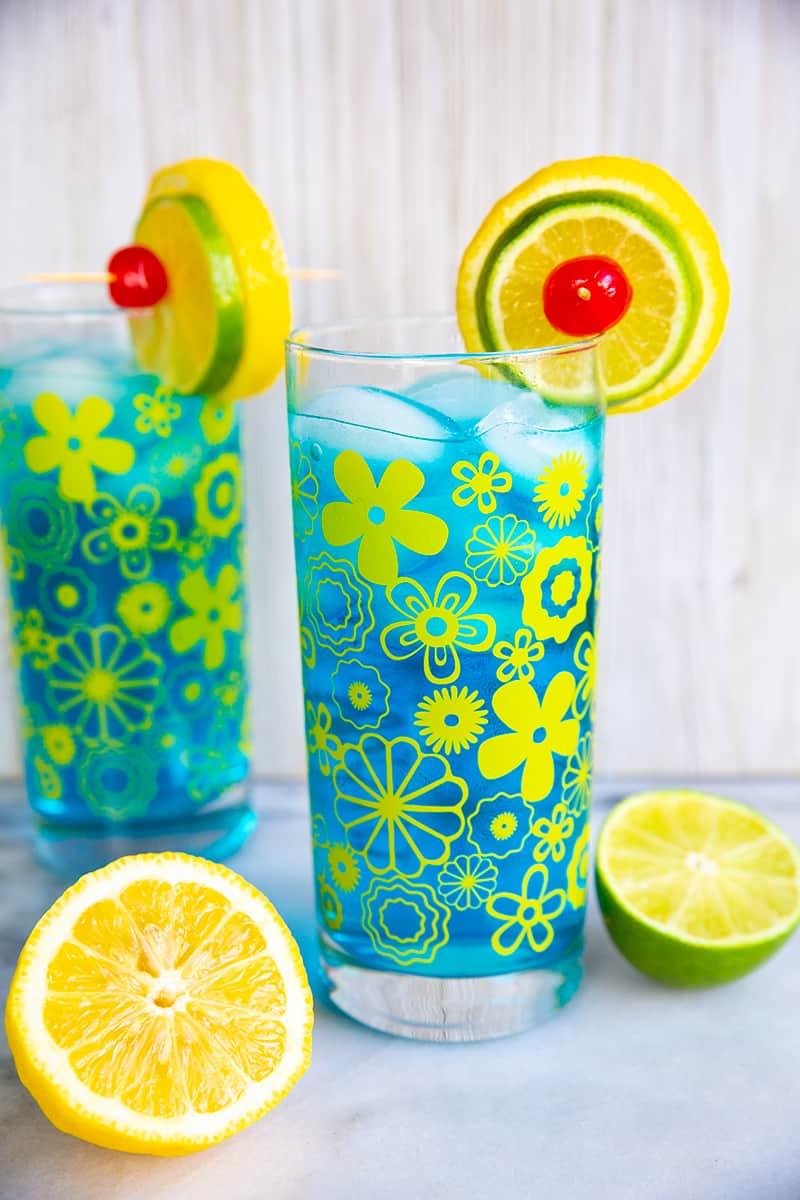close up Electric Lemonade cocktails side by side in vintage flower glasses garnish with lemon and lime