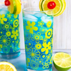 Two Electric Lemonade cocktails side by side in vintage flower glasses