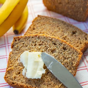 adding some spread into healthy banana bread slice using bread knife, ripe bananas and banana bread loaf on its background