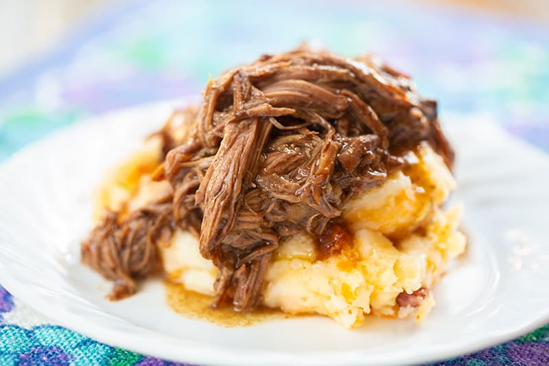 3 Ingredient Shredded Beef with mashed potatoes on a white serving plate, blue floral tablecloth underneath