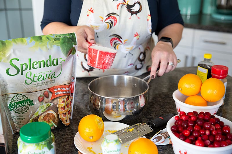 adding a cup of Splenda Stevia in a pot with water for cranberry sauce, all other ingredients on the table
