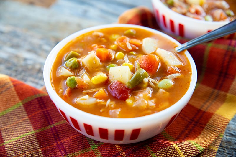 orange checkered tablecloth underneath a soup bowl filled with tomato based chicken vegetable soup with spoon