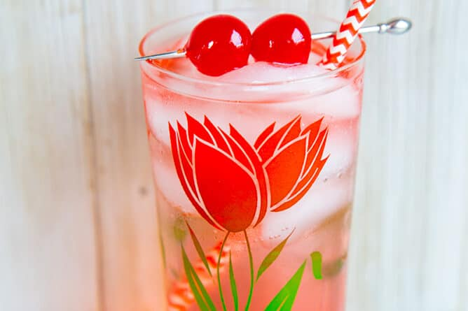 Dirty Shirley Cocktail in a glass with flower design, garnish with cherries