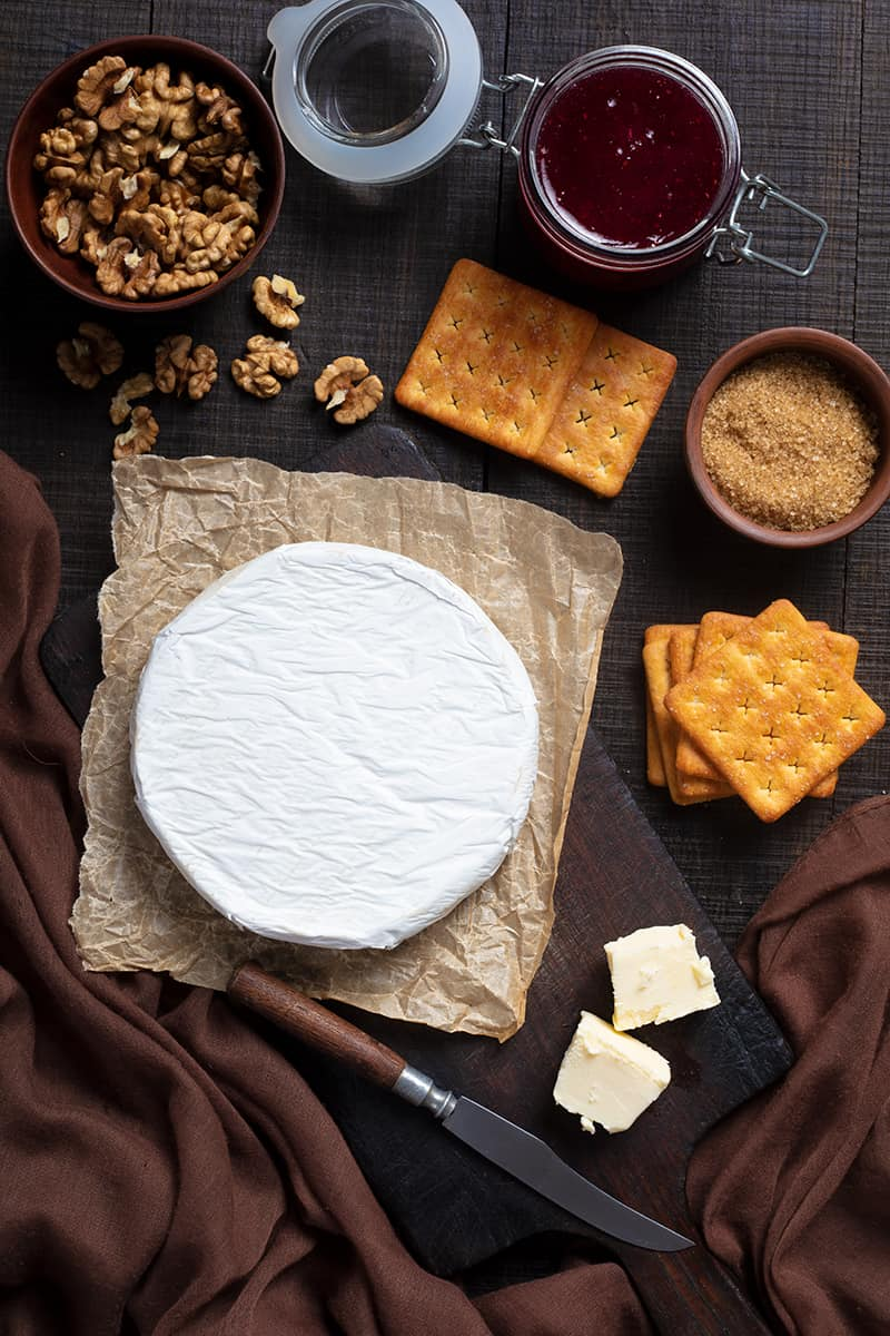 Walnut Raspberry Baked Brie ingredients on dark wood background with brown tablecloth on side