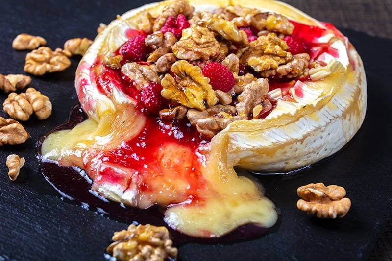 Walnut Raspberry Baked Brie in a black serving plate with raspberries and crunchy walnuts around