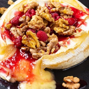 close up Walnut Raspberry Baked Brie in a black serving plate with raspberries and crunchy walnuts around