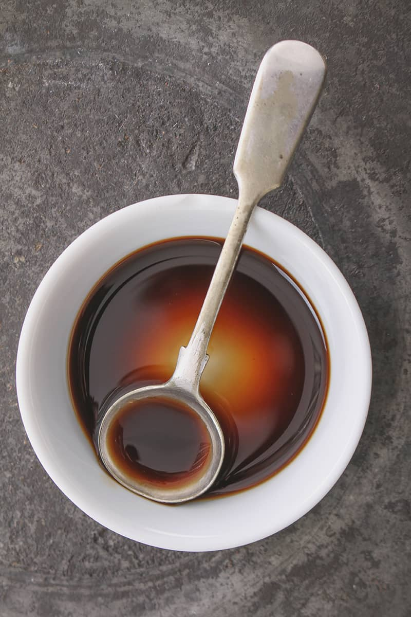Worcestershire Sauce in a white cup with stir spoon