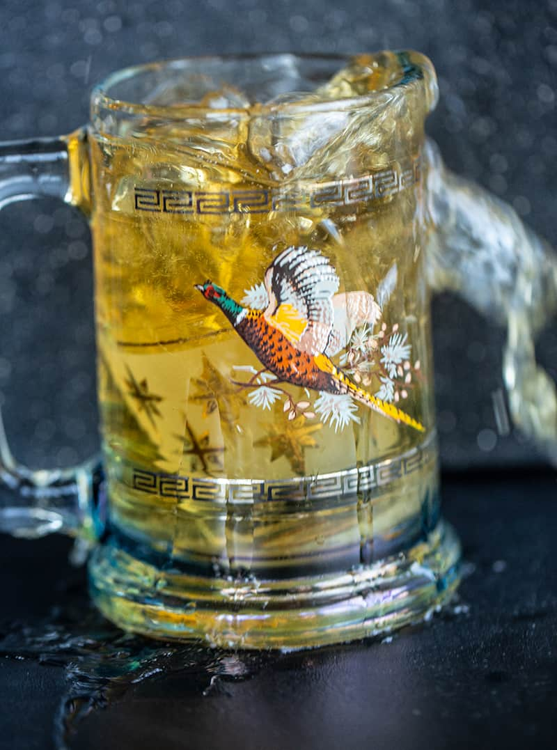 A shot glass of whiskey submerged in a glass of beer for a Boilermaker - spillage everywhere
