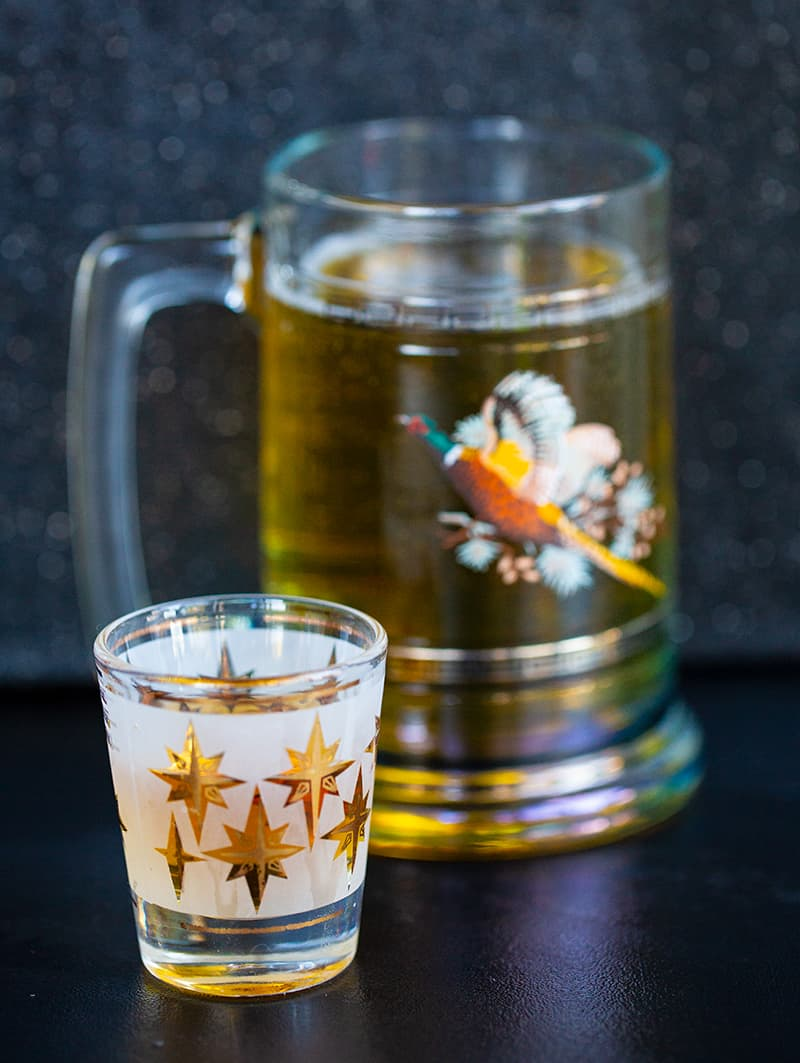 a shot glass with 1 ounce of whiskey and a glass of beer on background