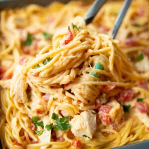 close up Cheesy Chicken Spaghetti in a pan with kitchen tongs