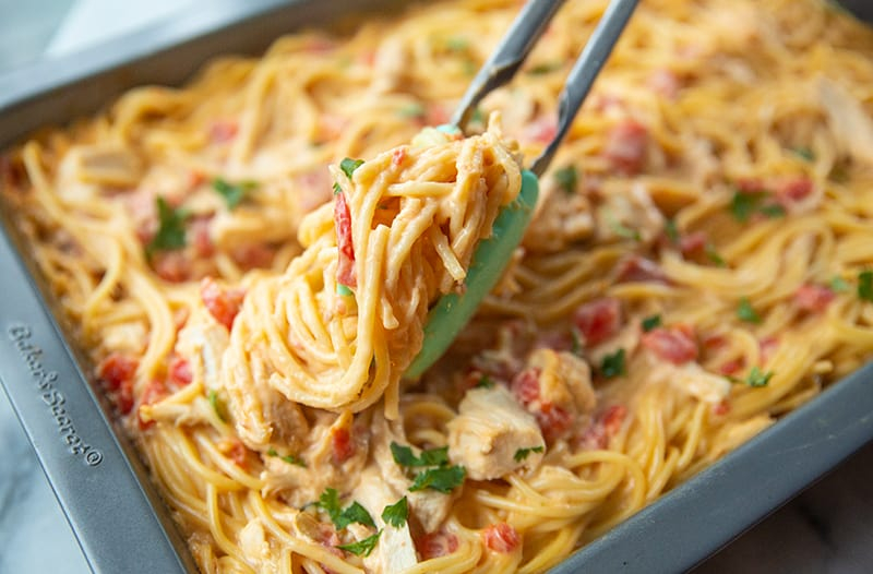 Cheesy Chicken Spaghetti in a pan with kitchen tongs