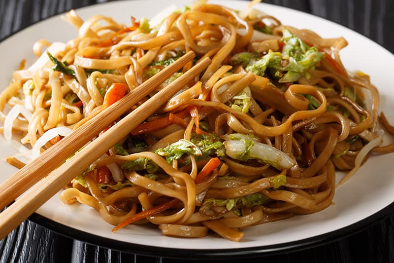 Pork Chow Mein in a white plate with chopsticks on top - Chow Mein vs Lo Mein