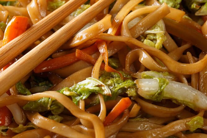 close up Pork Chow Mein in a white plate with chopsticks on top - Chow Mein vs Lo Mein