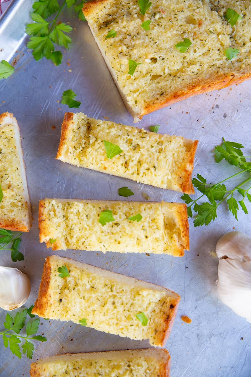 close up slices of Classic Homemade Garlic Bread in a baking sheet, pieces of garlic and some dried parsley leaves on its background