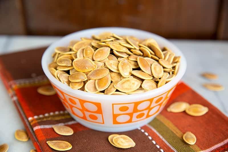 red orange kitchen cloth underneath a white bowl of Salty Crispy Roasted Pumpkin Seeds