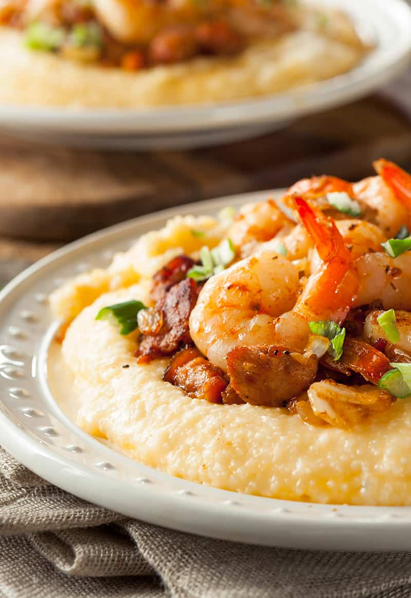 close up kitchen towel underneath white serving plate with Grits topped with shrimp and chopped spring onions