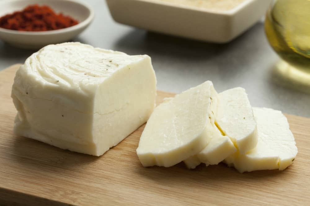 Piece of fresh sliced halloumi cheese on a cutting board