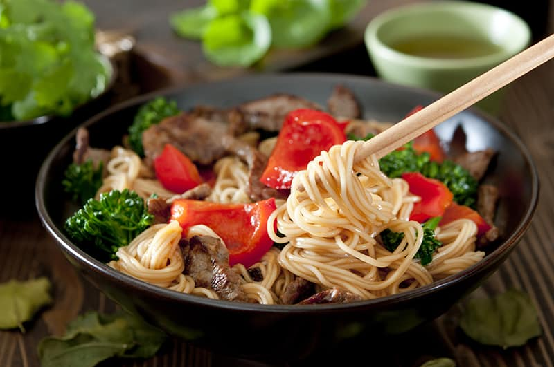 Beef and Vegetable Lo Mein in a black noodle bowl, pick up noodles using chopsticks