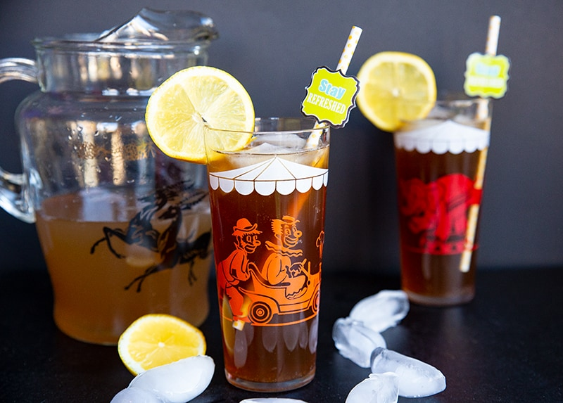 a pitcher and glasses of Long Island Iced Tea garnish with slices of lemon
