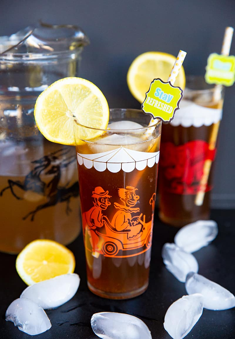close up glass of Long Island Iced Tea garnish with slice of lemon, a pitcher and another glass on its background