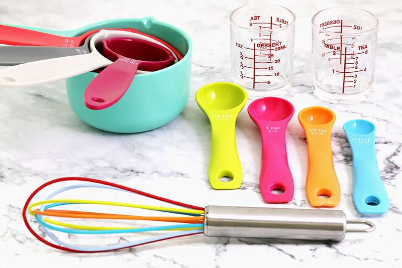 measuring and conversion cups used in kitchen and a colorful whisk tool