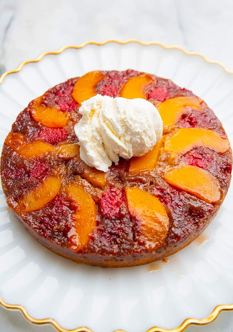 close up gold line dessert plate with Peach Upside Down Cake topped with a scoop of vanilla ice cream