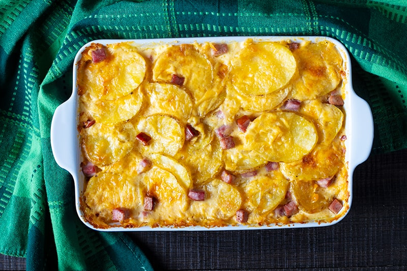 Scalloped Potatoes and Ham in a white casserole dish with green tablecloth underneath