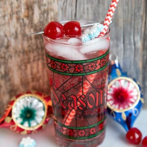 Sparkling vodka cranberry cocktail in a nice Christmas glass garnish with snowflakes and cherries