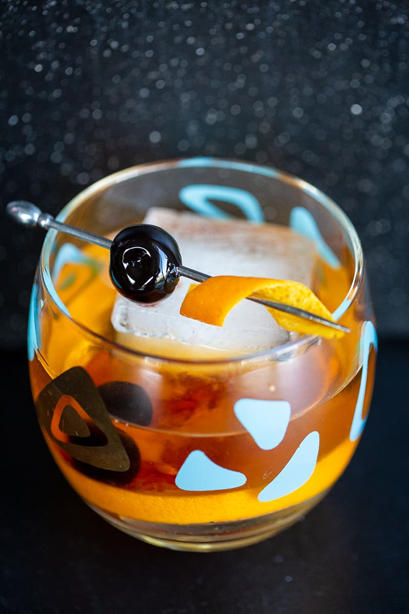 close up Old Fashioned cocktail in an old fashioned glass garnish with cherry and orange