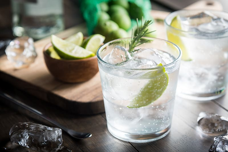tonic water and lime on a clear glass with some ice cubes, some slices of lime in a wooden cup on the background