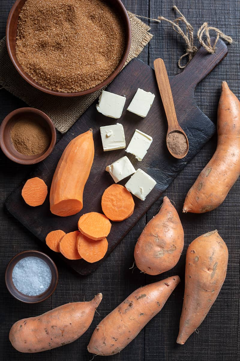 Candied Yams ingredients on chopping board and wood background