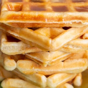 close up stack of fluffy Classic Waffle topped butter and maple syrup