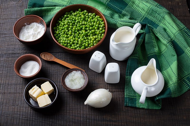 Creamed Peas ingredients on a wood background with green tablecloth
