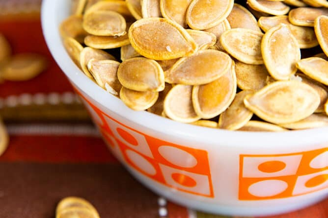 close up red orange kitchen cloth underneath a white bowl of Salty Crispy Roasted Pumpkin Seeds